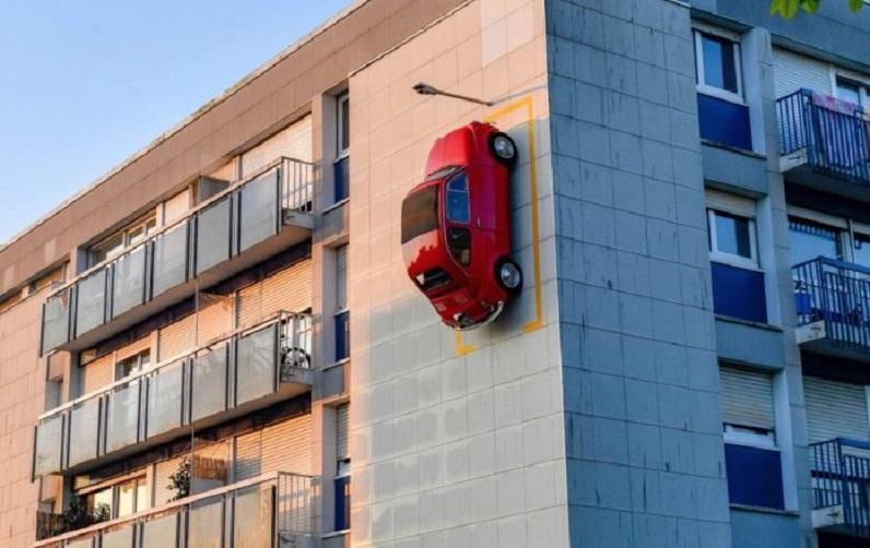 Red Fiat 500 parked on the facade of a building